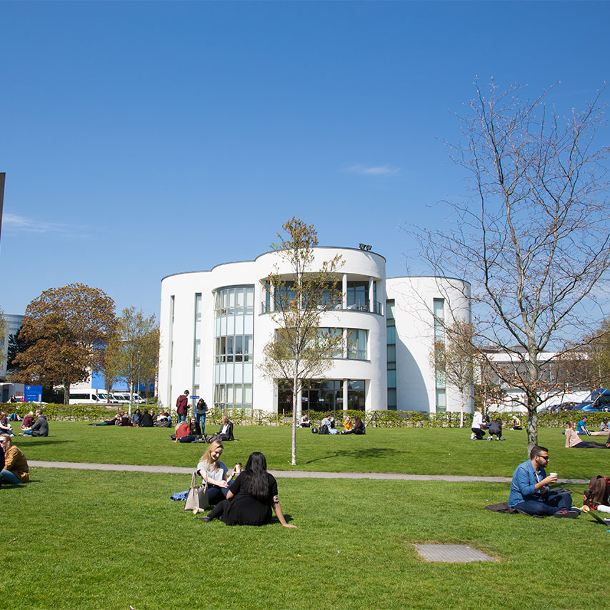 Image of students sitting outside the front of the University of Dundee campus.