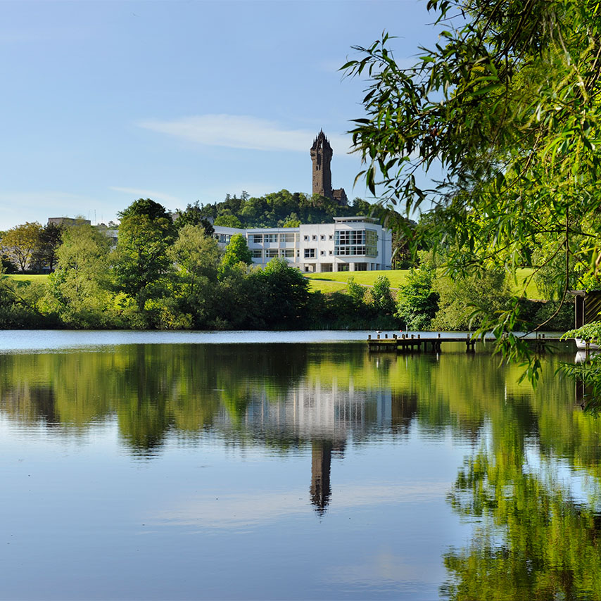 Image of the University of Stirling building across the grounds' lake.