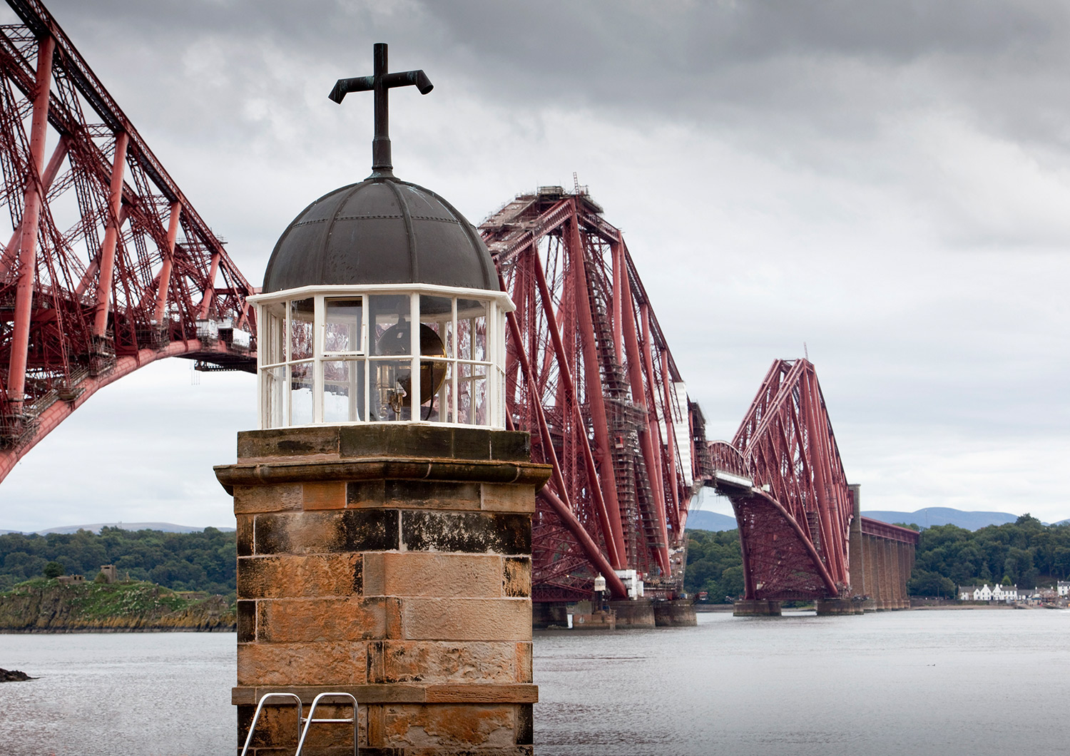 The top of a small light tower, with the Forth Bridge beyond.